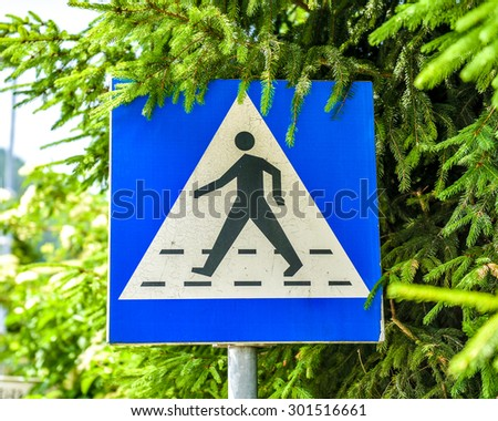 Old, weathered and violated pedestrian crossing sign in the street. Worn out sign with visible damage and dents covered with pine tree branches. - stock photo