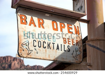 Old, weathered bar sign at vacant building - stock photo