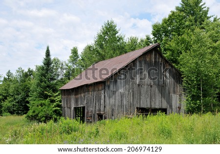 Old weathered barn in a field in rural Vermont - stock photo