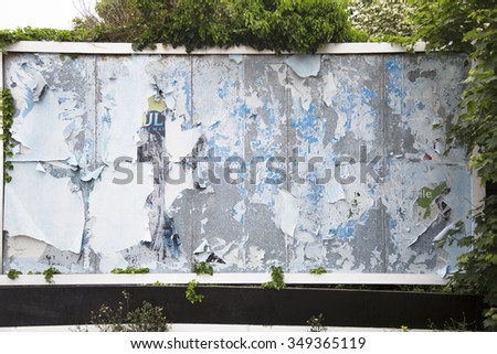 Old weathered billboard with peeling paper for advertisements of the past, surrounded by folliage. - stock photo