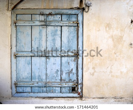 Old, weathered blue wooden window shutter on a orange wall - stock photo