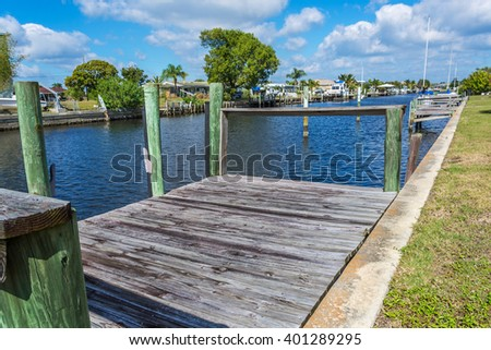 Old Weathered Boat Dock on a Canal in Florida. Southwest Florida homes on a canal.  View of canal homes and weathered boat dock along the rusty sea wall of the canal.  - stock photo