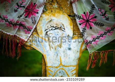 Old weathered crucifix on a wooden cross with cloth, along road in Romania - stock photo