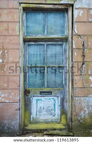 Old weathered door of an abandoned house - stock photo