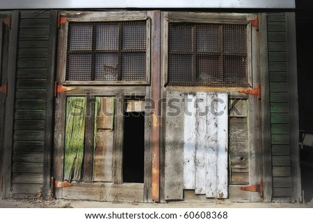 Old weathered door with a rusty grating and broken panel - stock photo