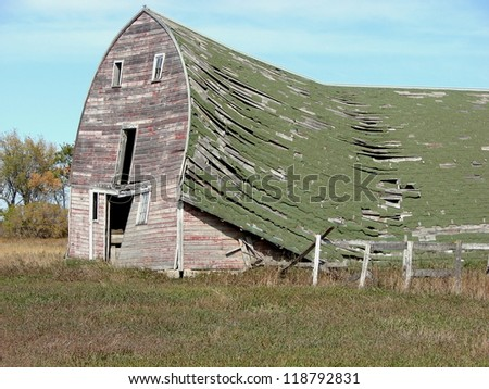old weathered farm building sagging roof - stock photo