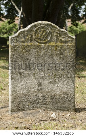 Old weathered gravestone in an ancient cemetery - stock photo