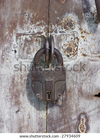 Old weathered iron garage door locked with rusted padlock - stock photo