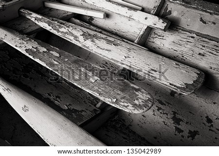 Old weathered oars in a large skiff - stock photo