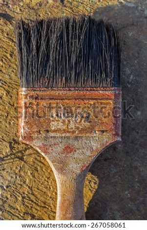 Old weathered paint brush on flat stone surface - stock photo