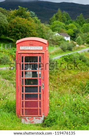Old weathered red telephone kiosk in Scotland - stock photo