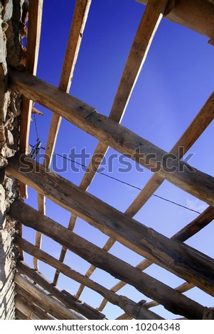 Old weathered roof construction frame under blue sky. - stock photo