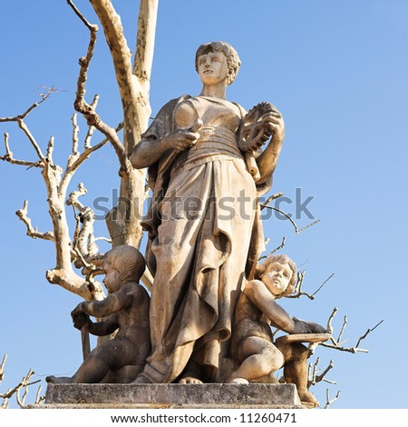 Old weathered statues on the old town square and marketplace in Aix-En-Provence, France. Outlined against a blue sky on a bright winter day - stock photo