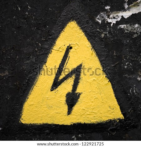 Old weathered triangle yellow high voltage sign - stock photo