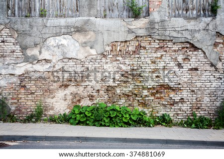 Old weathered wall of bricks and a ground  - stock photo