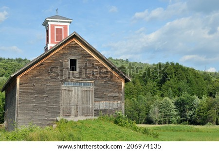 Old weathered wooden barn with a red cupola in a field in Vermont - stock photo