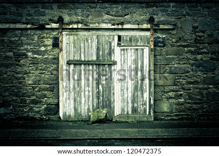 Old weathered wooden door in a wall in muted tones - stock photo