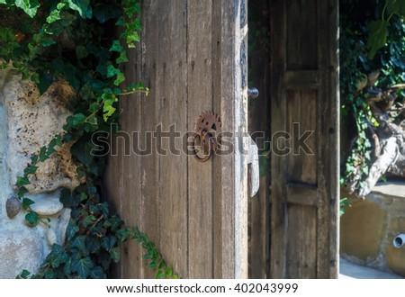 Old weathered wooden door with rusty handle. Rustic door. Shallow depth of field. Selective focus. - stock photo