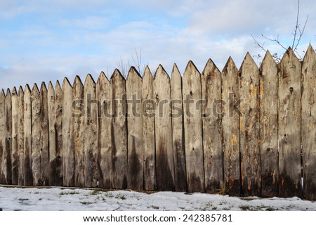 Old weathered wooden fence in the village, winter time - stock photo