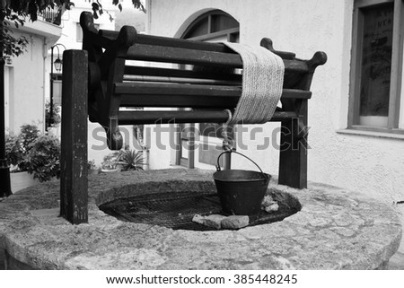 Old well in Malia town on Crete island, Greece. Black and white.