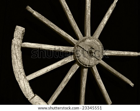 Old well wheel with sepia tone and black background. - stock photo