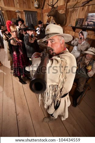 Old west cowboy and group point their weapons in a saloon - stock photo