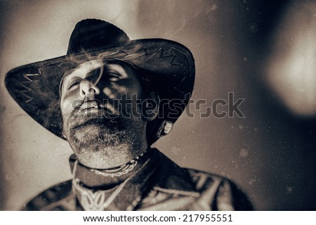 Old West Cowboy Smoke in the Eyes. An old west cowboy smoking a hand rolled cigarette, edited in vintage film style. - stock photo