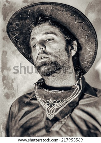 Old West Cowboy Tired. An old west cowboy looking tired with head up and face visible, edited in vintage film style. - stock photo