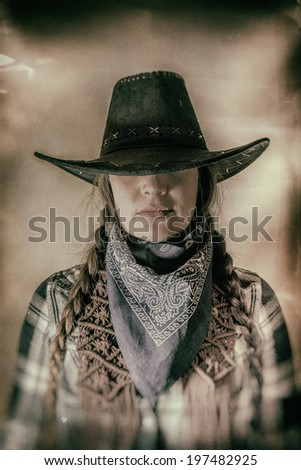 Old West Cowgirl Hat Low Wide. Old west cowgirl with hat low blocking eyes, edited in vintage film style. - stock photo
