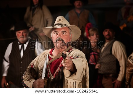 Old west hunter with dagger, scalps and gun - stock photo