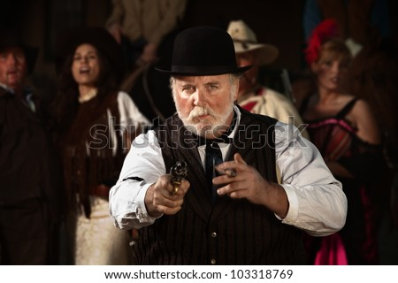 Old west hustler with cigar and gun drawn - stock photo