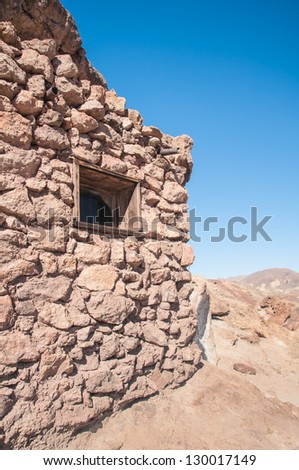 Old West Mining Shack in the California Desert under a bright blue sky - stock photo