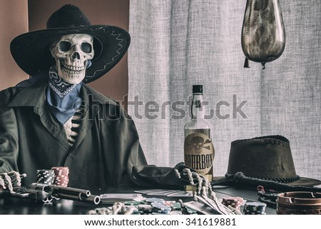 Old West Poker Skeleton Outlaw. Old west bandit outlaw skeleton at a poker table with a pistol and bourbon, edited in vintage film style. - stock photo