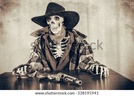 Old West Skeleton Revolver. Old west bandit outlaw skeleton at a poker table with a colt 45 pistol revolver edited in vintage film style. - stock photo