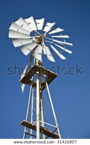 Old west-style farm windmill for pumping water  with spinning blades against a blue sky with  clouds.