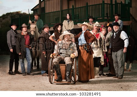 Old west theme Senior couple with group of people - stock photo