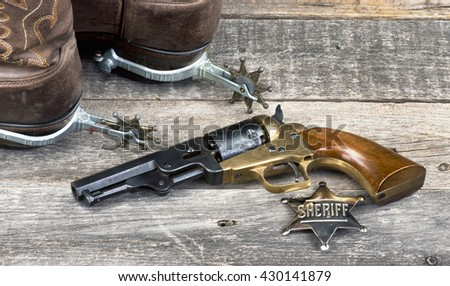 Old western pistol, badge, spurs and cowboy boots. - stock photo