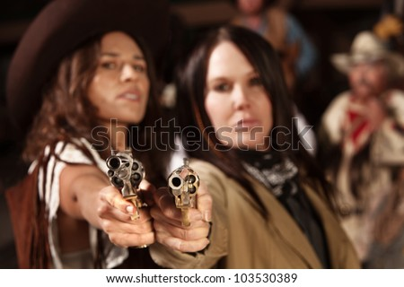 Old western revolvers held by beautiful gun fighters - stock photo