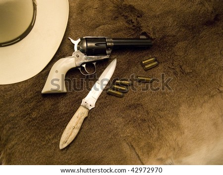 Old Western Weapons showing a hat, a gun, bullets and a knife on top of an old deer skin