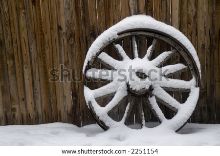 Old Wheel in Snow - stock photo