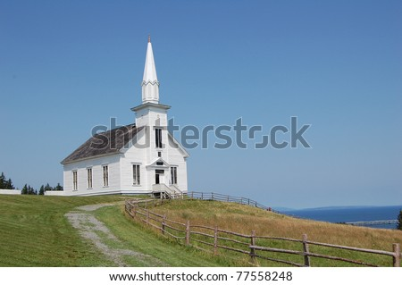 old white church in nova scotia, canada, overlooking the sea on summer's day - stock photo
