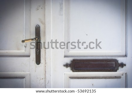 Old white doors with handle and name plate.