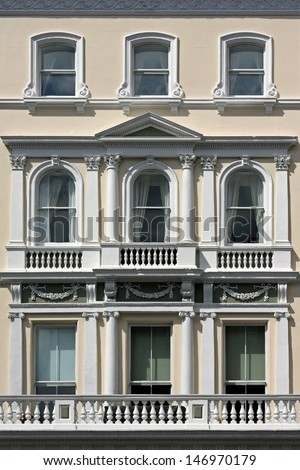 Old white facade building with windows and balconies - stock photo
