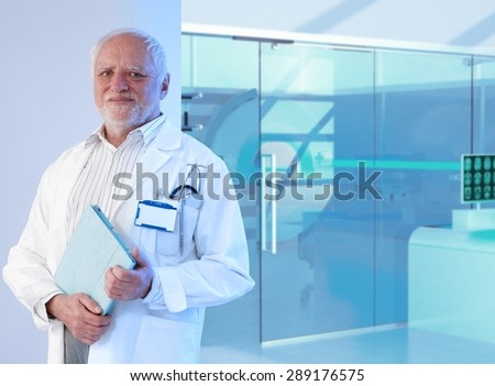Old white haired professor doctor standing in front of MRI room at hospital, holding tablet, smiling. - stock photo