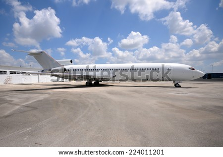 Old white jet airplane sitting on a tarmac - stock photo