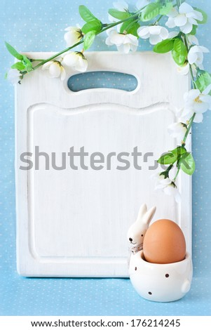 Old white kitchen cutting board with copy-space for writing Easter menu, funny rabbit egg cup and blossom apple tree. - stock photo