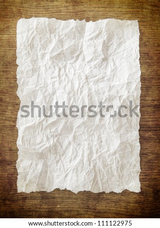 Old white paper sheet on wooden table - stock photo