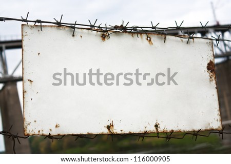 Old white plate on a barbed wire fence - stock photo