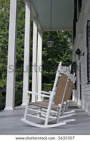 Old white rocking chairs on a colonial porch with white columns