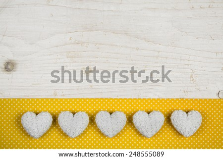 Old white shabby chic background with five hearts and yellow fabric on the frame. - stock photo